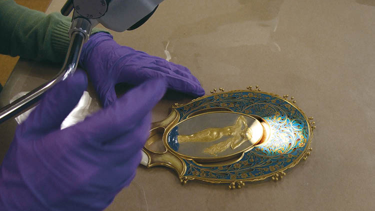 A mirror designed by Félix Bracquemond with a relief by Auguste Rodin undergoes examination in the objects lab.