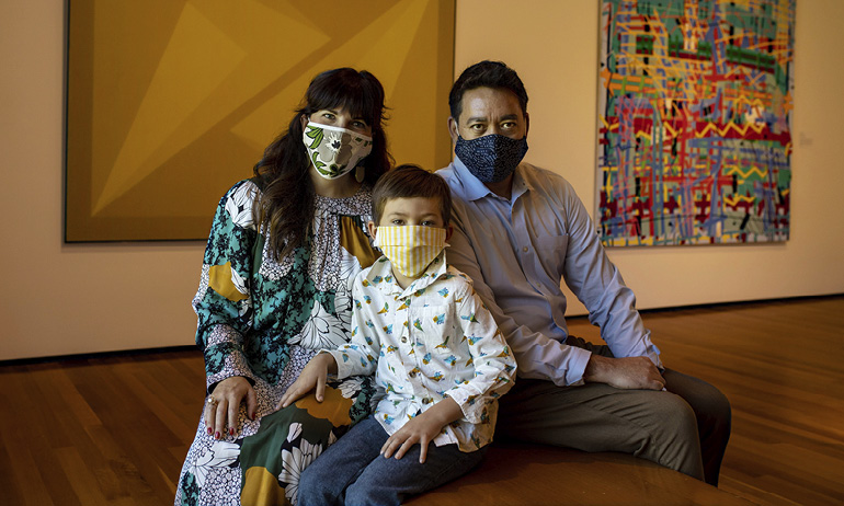 A woman and man seated with their son in a gallery of contemporary art