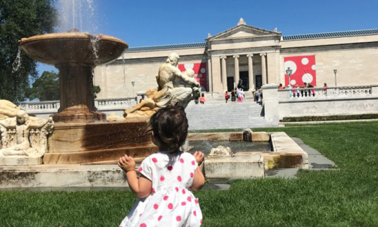 A young child gazes at the water fountain in front of the Cleveland Museum of Art
