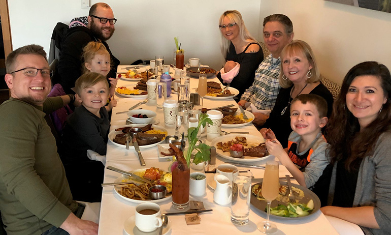 A large family smiles as they sit around a long table filled with food