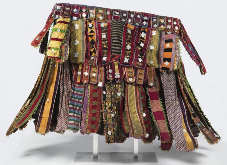 Egúngún Masquerade Dance Costume (paka egúngún) c. 1920–48.  Yoruba. Cotton, wool, wood, silk, synthetic textiles (including viscose rayon and acetate), indigo, and aluminum; approx. 139.7 x 15.2 x 160 cm. Brooklyn Museum, Gift of Sam Hilu, 1998.125