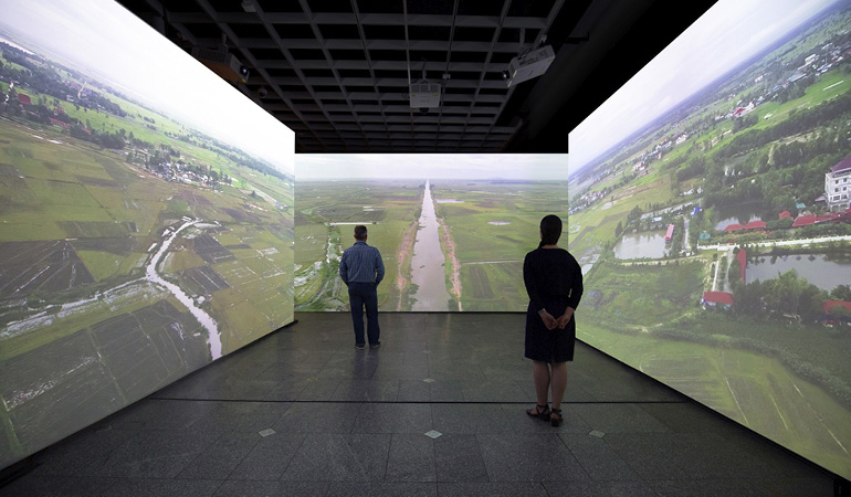 two people standing among three wall sized projections of a landscape