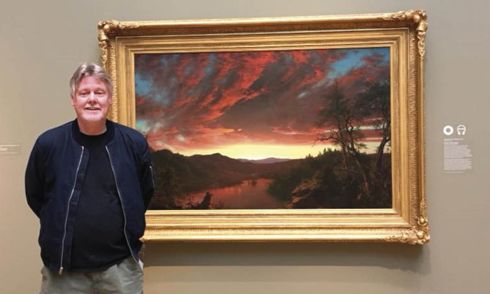 "A man stands next to the painting ""Twilight in the Wilderness"" by Frederic Church"