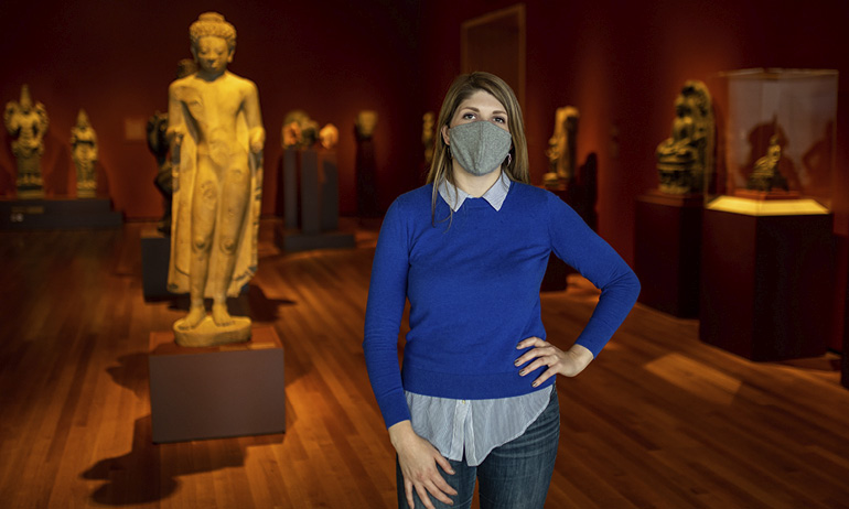 A woman standing in a gallery displaying several Asian sculptures