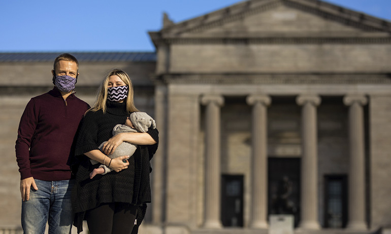 A woman holding an infant and standing beside a man in front of the Cleveland Museum of Art