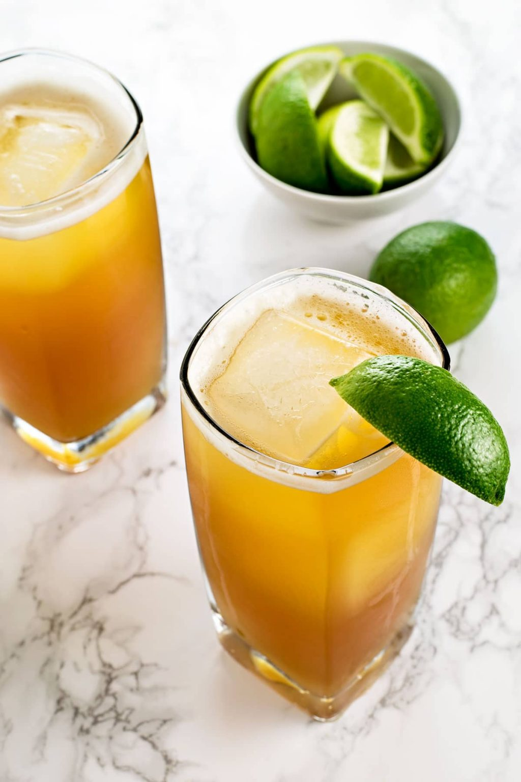 A glass filled with an orange mixed drink with ice, garnished with a lime wedge