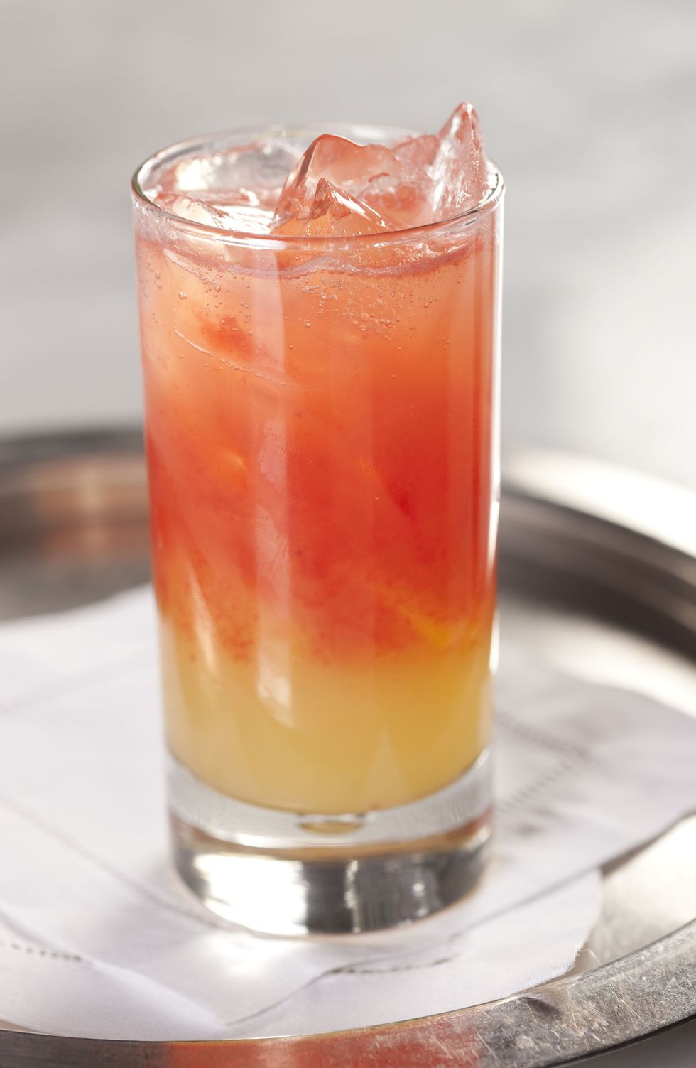 A pink and golden hued drink in a tall glass with ice