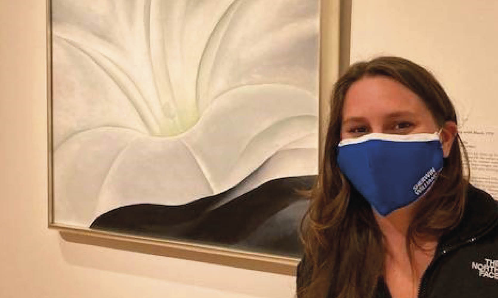 "A teenage girl wears a mask standing next to the painting ""Morning Glory with Black"" by Georgia O'Keeffe"