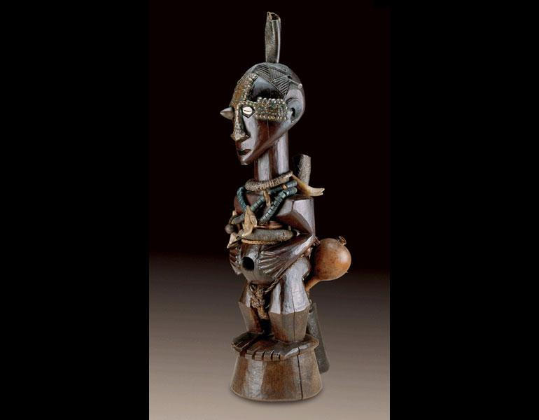 Male figure. Songye, D.R.C. Wood, brass, iron, glass beads, cowrie shell, leopard's teeth, gourd, reptile skin, fiber; h. 66 cm. Possibly field-collected by W. F. P. Burton in 1927–35. National Museum of African Art, Smithsonian Institution, Washington [museum purchase and gift of Professor David Driskell, Friends of the National Museum of African Art, Robert and Nancy Nooter, Milton F. and Frieda Rosenthal, Honorable and Mrs. Michael Samuels, and Mr. Michael Sonnenreich] (86–4-1). Photo: © National Museum