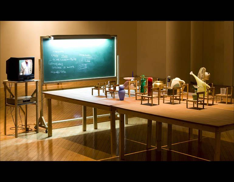Objects Being Taught They Are Nothing But Tools, 2010. Kim Beom (Korean, b. 1963). Daily objects, wooden chairs, blackboard with fluorescent light, wooden tables, single channel video on TV monitor (21 min., 8 sec.); approx. 165.5 x 427.5 x 230 cm (overall). Courtesy of the artist. © Kim Beom. Photo by Park Myung-Rae