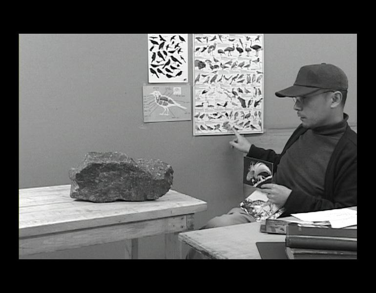 Video still of A Rock That Was Taught It Was a Bird, 2010. Kim Beom (Korean, b. 1963). Stone, wood, wooden table, single channel video on 12-inch flat monitor (1 hr., 27 min., 30 sec.); approx. 146.8 x 220.5 x 127.7 cm (overall). Courtesy of the artist. © Kim Beom