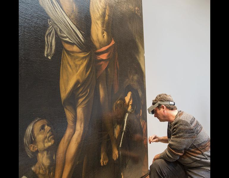 Conservator of Paintings Dean Yoder examines The Crucifixion of Saint Andrew by Caravaggio. Photograph by Howard Agriesti