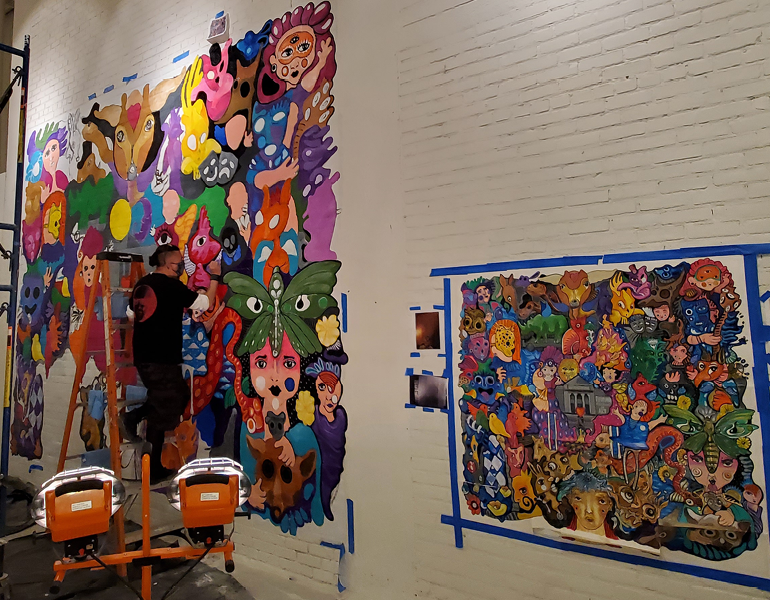 An artist painting a mural at the CMA Community Arts Center