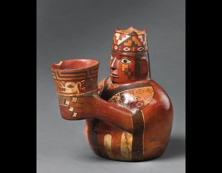 "Cup-Holding Figure in Tie-Dyed Tunic and Four-Cornered Hat, 600–1000. Peru, Wari. Ceramic and slip; 19.3 x 19.5 cm. Museo Regional de Ica ""Adolfo Bermúdez Jenkins"" MRI-00176-01. Photo: Daniel Antonio Giannoni Succar"