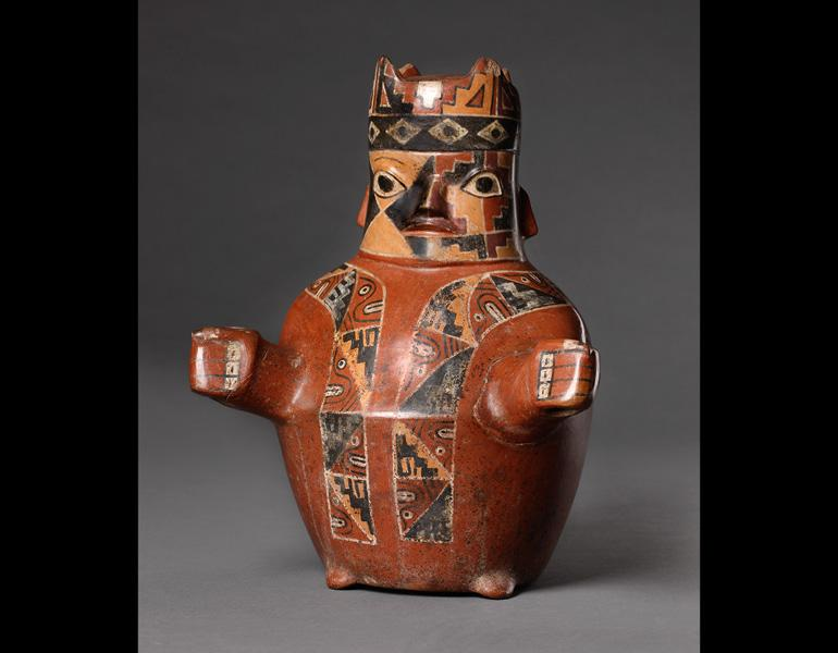 Figure in Tapestry-Woven Tunic and Four-Cornered Hat, 600–1000. Peru, Wari. Ceramic and slip; 28.7 x 23 cm. Fundación Museo Amano, Lima FMAC-000020. Photo: Daniel Antonio Giannoni Succar