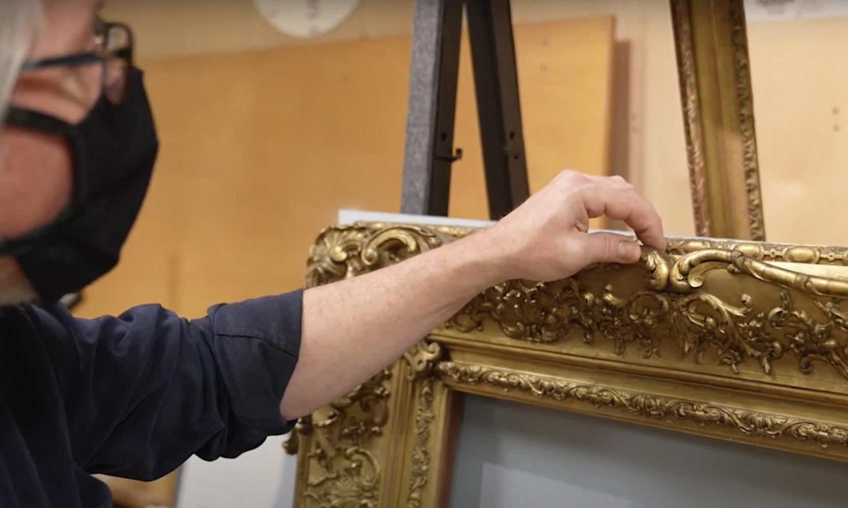 hand touching the edge of a gilded frame