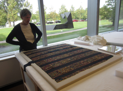 Textile conservator Robin Hanson viewing tunic fragments